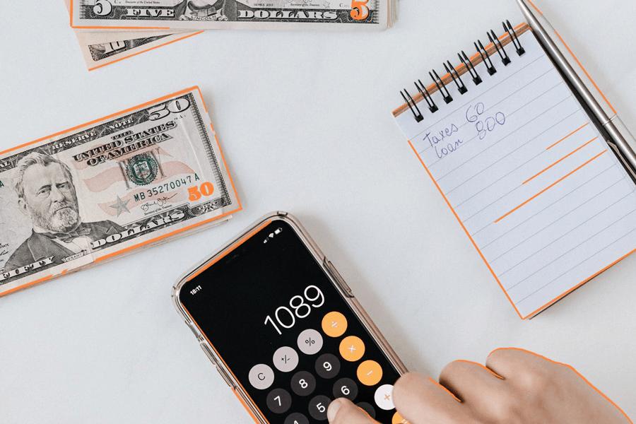 Persona haciendo cálculos de impuestos e importe total en su factura con calculadora