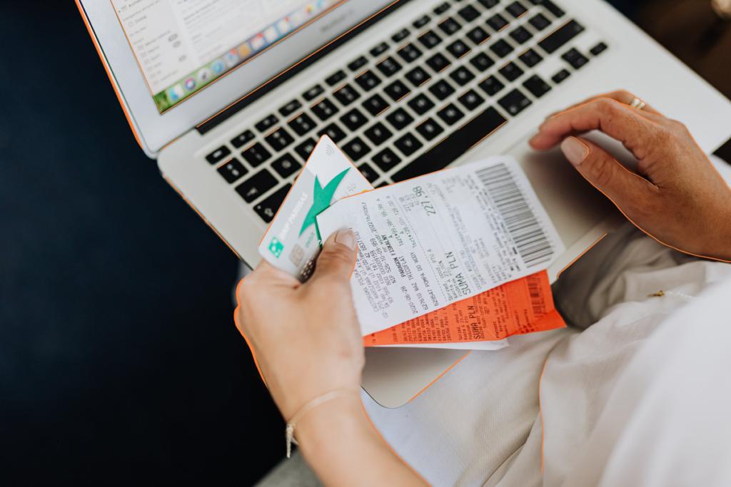 Persona con tickets y portátil pensando en cómo hacer una factura